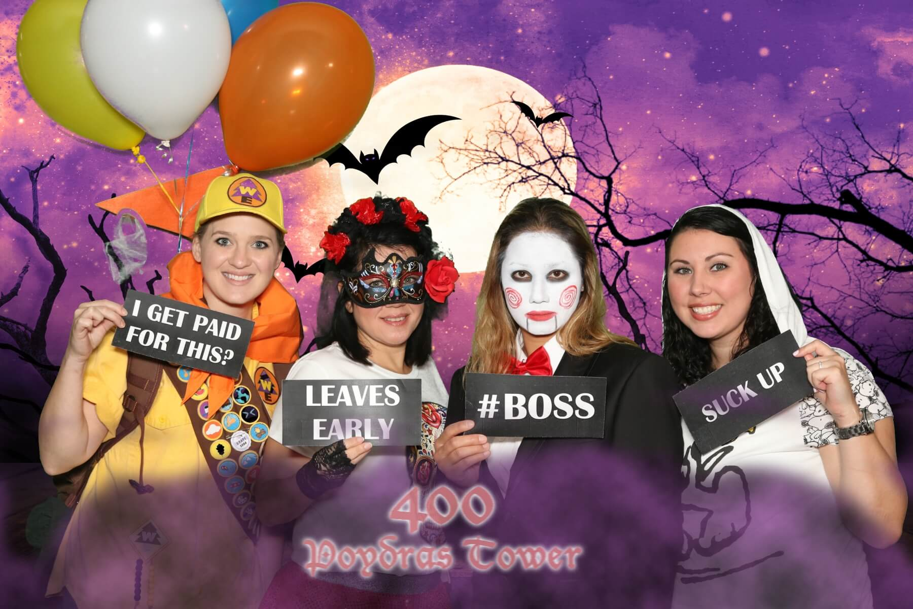 Four young women holding silly signs for a halloween inspired event photo booth rental
