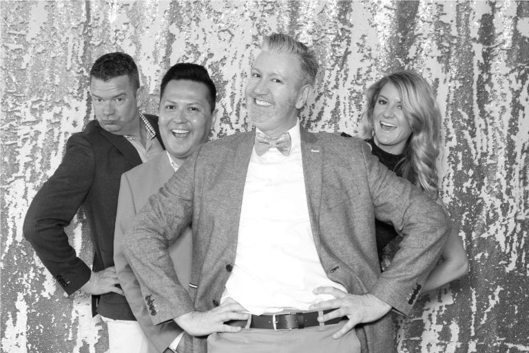 3 men and 1 woman posing silly for a photo booth in black and white